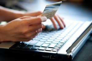 Individual making an online purchase using a credit card and laptop