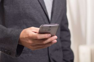 Man using a mobile device. Bring Your Own Device is the practice of using a personal mobile device for work purposes.