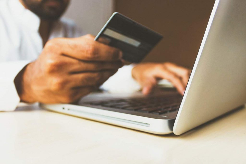 Man making an online credit card payment. One method of how hackers attack small businesses.